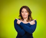 Confused young woman pointing with fingers in two different directions. Portrait confused young woman pointing with fingers in two different directions, not sure Royalty Free Stock Image