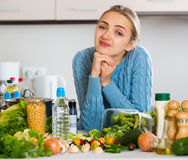 Confused young woman recalling recipe for dinner in kitchen Royalty Free Stock Photos