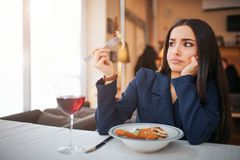 Confused young woman sit at table and look at piece of salad she hold. Her sight is weird. Youhng woman sit in royalty free stock images