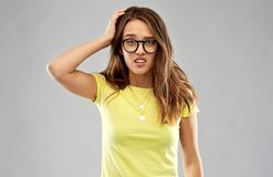Confused young woman or teenage girl in glasses stock image