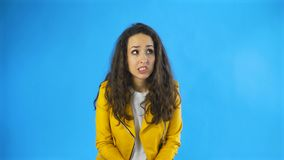 Confused young woman in yellow jacket in studio with blue background. 4K stock footage