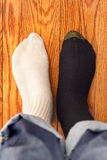 Confusing socks. Men in two color socks on the wood floor. Confusing Stock Photos
