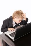 Confusion. Little boy in a business suit with the laptop in the confusion, isolated Stock Photo