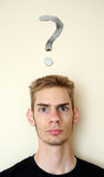 Confusion. Young white Caucasian male adult staring forward, confused, with a question mark above his head on the wall behind him. Focus point is on the person Royalty Free Stock Photo