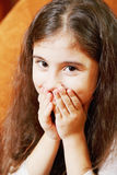 Confusion. Little brunette girl with long hair closing mouth with hands in confusion Stock Images