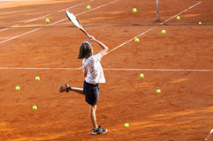 Confusion. Outdoor image of girl trying to hit tennis balls Stock Photography
