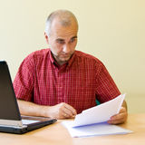 Confusion. Confused office worker studying agreement at the desk with laptop stock image