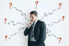 Confusion and challenge concept. Portrait of attractive young european businessman with drawn question marks. Confusion and challenge concept royalty free stock image