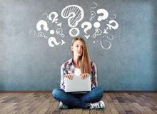 Confusion concept. Attractive young woman sitting on wooden floor with laptop and drawn question marks above on concrete wall. Confusion concept Royalty Free Stock Image