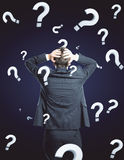 Confusion concept. Back view of stressed young businessman on dark background with question marks. Confusion concept Royalty Free Stock Photo