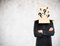 Confusion concept. Businessman with folded arms and cardboard box with question marks covering head on concrete background. Confusion concept Royalty Free Stock Image