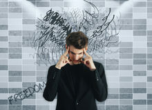 Confusion concept. Pensive young businessman on tile background with scribble. Confusion concept Stock Image