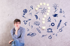 Confusion concept. Pensive young man on concrete background with educational sketches and sticker question mark. Confusion concept Stock Photography