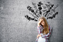 Confusion concept. Pensive young woman on concrete background with scribble. Confusion concept Stock Photography