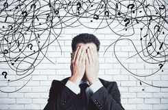 Confusion concept. Stressed young businessman with scribble and question marks on white brick background. Confusion concept Royalty Free Stock Photo