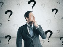 Confusion and doubt concept. Portrait of thoughtful young european businessman with question marks. Confusion and doubt concept stock image