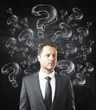 Confusion and doubt concept. Thooughtful young businessman with question marks standing on chalkboard background. Confusion and doubt concept Royalty Free Stock Photos