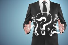 Confusion and faq concept. Businessman holding question marks on blue background. Confusion and faq concept Stock Images
