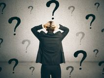 Confusion and uncertainty concept. Back view of young businessman on concrete wall background with question marks. Confusion and uncertainty concept royalty free stock photography