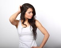 Confusion unhappy brunette woman thinking and scratching the hea. D in white t-shirt on white copy space background Royalty Free Stock Photo