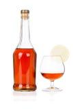Congac Flasche mit Glas und Kalk auf Weiß Lizenzfreie Stockfotos