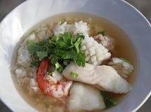 Congee риса смешал с креветкой, рыбой, кальмаром и свинина, гарнирует с кориандром стоковая фотография rf