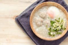 Congee asiático con cerdo y el huevo picaditos en el cuenco blanco Imagenes de archivo