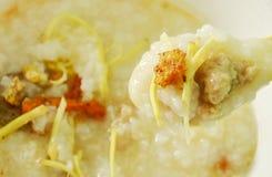 Congee do arroz com carne de porco e o gengibre triturados da fatia na colher de sopa Imagem de Stock