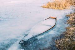 Congelé dans la glace de la rivière, le lac, accumulent le vieux bateau en bois abandoné a Photo libre de droits