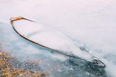 Congelé dans la glace de la rivière, le lac, accumulent le vieux bateau en bois R abandoné Photos libres de droits