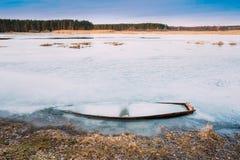 Congelé dans la glace de la rivière, le lac, accumulent le vieux bateau en bois R abandoné Image libre de droits