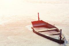 Congelado en el hielo del río, el lago, acumula el barco de madera viejo Fotos de archivo
