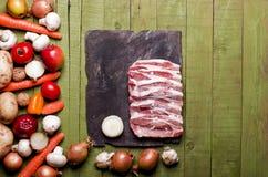 Congelato crudo su fondo di legno verde Collo crudo, veget della carne di maiale Immagini Stock Libere da Diritti