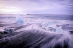 Congele na praia no lago da geleira de Jokulsarlon no nascer do sol Fotografia de Stock
