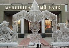 Congele o arco com um boneco de neve e uma cabra antes de uma entrada no banco municipal de Cacánia, Abacã Imagem de Stock Royalty Free