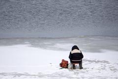 Congele o pescador na pele de raposa do lago da montanha do inverno imagem de stock