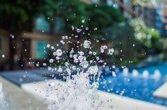 Congele salpicando gotitas del agua en el aire cerca de la piscina Imagenes de archivo