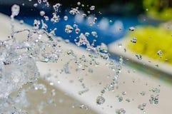 Congele salpicando gotitas del agua en el aire cerca de la piscina Imágenes de archivo libres de regalías