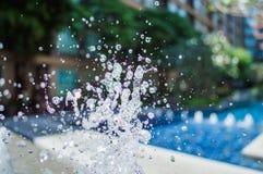 Congele salpicando gotitas del agua en el aire cerca de la piscina Fotografía de archivo