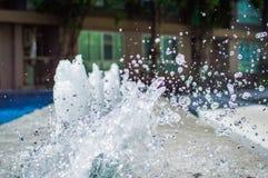 Congele salpicando gotitas del agua en el aire cerca de la piscina Foto de archivo