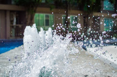 Congele-se espirrando gotas da água no ar perto da piscina Foto de Stock
