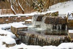 Congele sincelos em uma fonte de congelação no inverno fotografia de stock