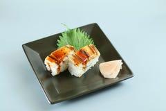 Conger eel sushi. On a black plate Stock Photos