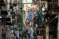 Congested Italian street. Typical Italian alley with clothes hanging from the drying racks, and flags dangling between buildings. A very busy looking street Royalty Free Stock Images