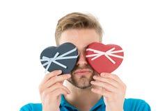Congettura quale L'uomo tiene due cuore a forma di contenitori di regalo davanti agli occhi, fondo bianco Romantico pronto macho fotografia stock
