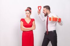 Conglict. Woman ignore man, businessman roar, holding gift and h. Eart. Indoor, studio shot,  on gray background Royalty Free Stock Images