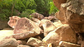 Conglomeration of Large Brown Boulders by River in Park stock footage
