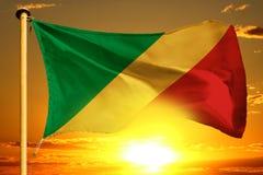 Congo flag weaving on the beautiful orange sunset background. Creative still royalty free stock photo