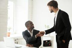 Congra africano degli impiegati di handshake esecutivo caucasico riconoscente immagini stock