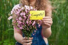 Congrats -有桃红色花卡片和花束的美丽的妇女  免版税图库摄影